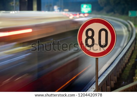 Long exposure shot of traffic sign showing 80 km/h speed limit on a highway full of cars in motion blur during the night #1204420978