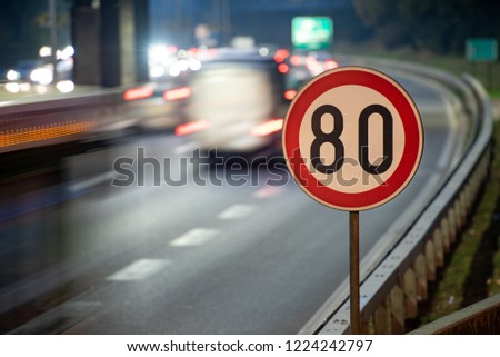 Long exposure shot of traffic sign showing 80 km/h speed limit on a highway full of cars in motion blur during the night #1224242797