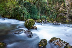 Long exposure smooth flowing water over rocks in forest