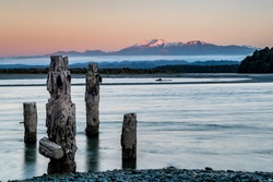Long Exposure sunrise with mountain background and dilapidated old dock in the foreground all set in an aqua turquoise lake