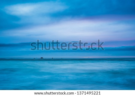 Long exposure sunset seascape of a Nova Scotia beach at dusk.  Beautiful colors are on display to highlight the sand, rocks, seaweed and barnacles. #1371495221