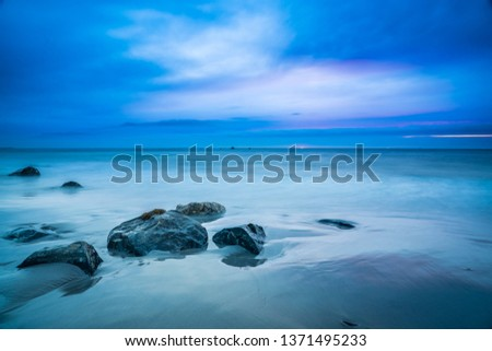 Long exposure sunset seascape of a Nova Scotia beach at dusk.  Beautiful colors are on display to highlight the sand, rocks, seaweed and barnacles. #1371495233