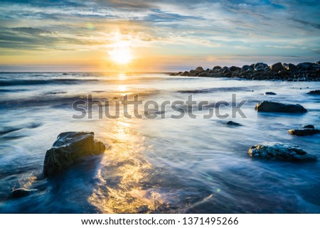Long exposure sunset seascape of a Nova Scotia beach at dusk.  Beautiful colors are on display to highlight the sand, rocks, seaweed and barnacles. #1371495266