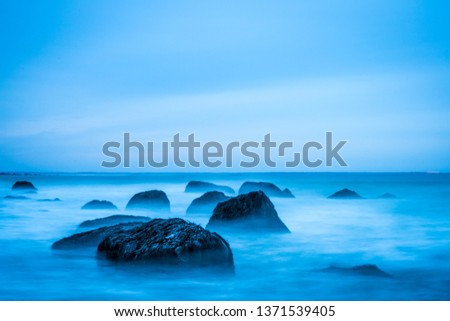 Long exposure sunset seascape of a Nova Scotia beach at dusk.  Beautiful colors are on display to highlight the sand, rocks, seaweed and barnacles. #1371539405