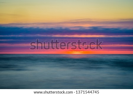 Long exposure sunset seascape of a Nova Scotia beach at dusk.  Beautiful colors are on display to highlight the sand, rocks, seaweed and barnacles. #1371544745