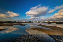 Long exposure view of tidal channel at low tide with reflection of cloud on the sea at Yeongjongdo Island near Incheon, South Korea