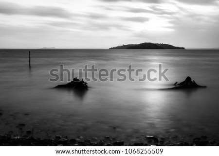 Long exposure view of Trasimeno lake (Umbria) shore, with branches, stones and poles beneath a cloudy sky filtering the sunset #1068255509