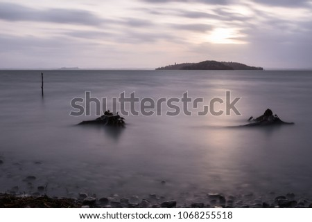 Long exposure view of Trasimeno lake (Umbria) shore, with branches, stones and poles beneath a cloudy sky filtering the sunset #1068255518
