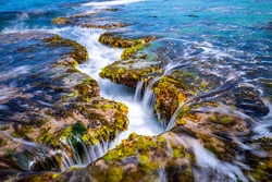 Long exposure view of wave and waterfall on sea rock with green laver at Mopo-ri near Pohang-si, South Korea