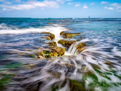Long exposure view of wave and waterfall on sea rock with green laver with the background of sea horizon at Mopo-ri near Pohang-si, South Korea
