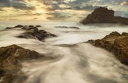 Long exposure water, beautiful seascape, ocean views, rocky coastline, sunlight, on the horizon. Composition of nature. Sunset scenery background. Cloudy sky. California coast.