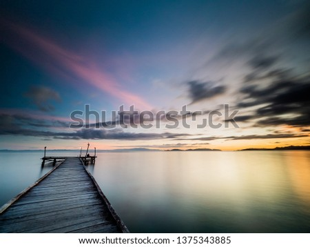 Stock Photo Long exposure wide angle image taken at twilight and viewed from a wooden jetty. Silky smooth water and soft clouds with dark blue and purple hues and orange at at the horizon, cloud movement visible