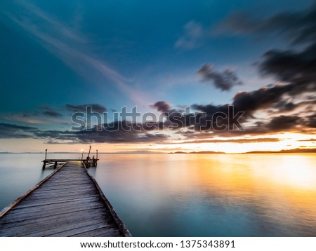 Stock Photo Long exposure wide angle shot of a jetty at twilight. Silky smooth water and soft clouds with dark blue and purple hues and bright orange sunlight overexposed at at the horizon