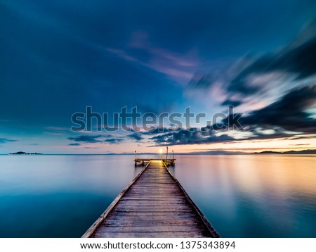 Stock Photo Long exposure wide angle twilight image viewed from a wooden jetty. Jetty in the center of image. Silky smooth water and soft clouds with dark blue and purple hues and orange at at the horizon