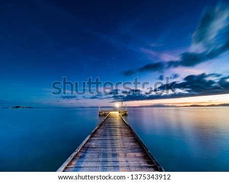 Stock Photo Long exposure wide angle twilight image viewed from a wooden jetty. Silky smooth water and soft clouds with dark blue and purple hues and orange at at the horizon