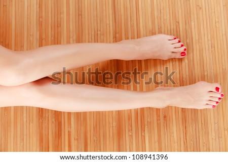 Long female legs on wooden floor