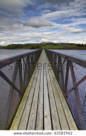 Long footbridge stretching into the distance across a wide lake