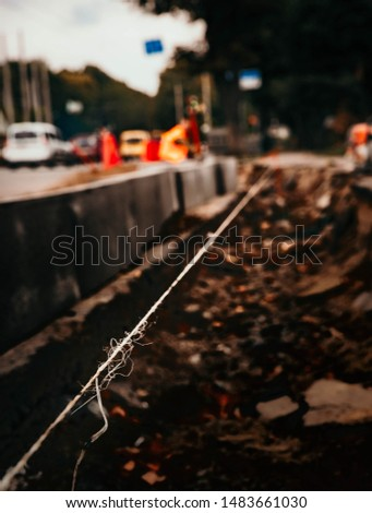 Long frayed rope near to break. On earth background. White thread that breaks.