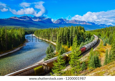 Photo of  Long freight train moving along Bow river in Canadian Rockies ,Banff National Park, Canadian Rockies,Canada.
