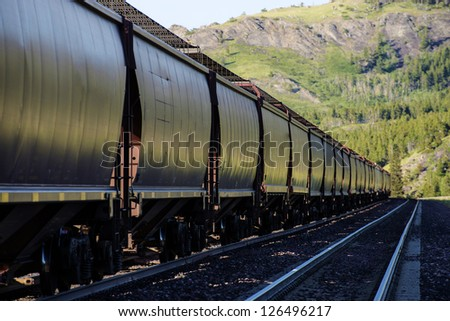 Long freight train with hopper cars parked on railroad siding