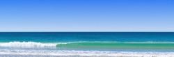 long glassy wave breaking along the beach