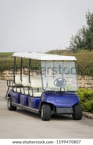 Long golf electric cart parked on parking. Empty shuttle eight seat electro car #1199470807