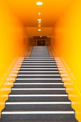 Long gray stairs with many steps in a high building with yellow wall