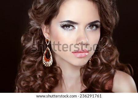 Long hair. Beautiful brunette girl model with fashion earrings. Makeup, luxury jewelry, wavy hairstyle. Woman isolated over dark studio background.