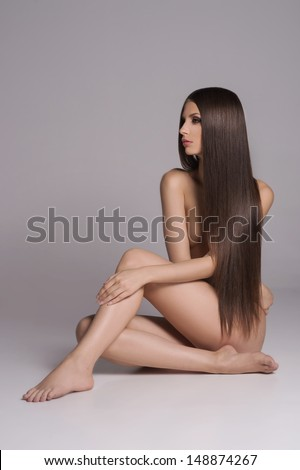 Long hair beauty Attractive naked women with beautiful hair sitting on the floor and looking away while isolated on white