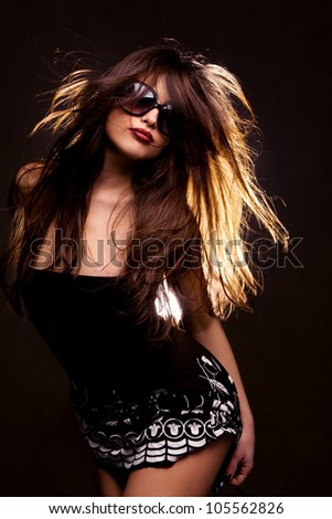 long hair brunette with sunglasses dancing, studio black background