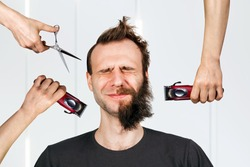 long hair freak crazy man hold scissors and trimmer and guy want cut his hair at home. Concept for barbershop.