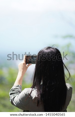 Long hair girl is shooting video of beautiful nature view on cell telephone. Female tourist is taking photo with mobile phone camera Woman taking photo.