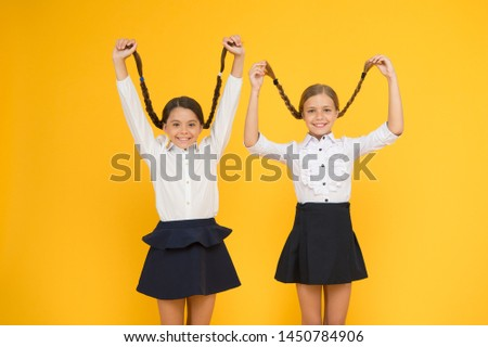 Long hair growth stimulant. Cute small children holding long hair braids on yellow background. Adorable little girl being proud of long hair. Wearing long hair in plaits for school.