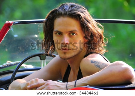 stock photo : long hair male model sitting in a red convertible classic