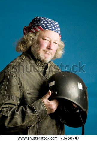 long hair senior motorcycle man wearing leather jacket and American flag bandana motorcycle helmet - stock photo