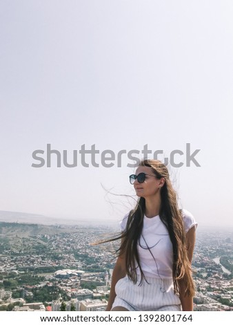 Long hair woman turned head to city panoramic view. Girl in white clothes. Freelance lifestyle concept. Waving hair on the wind. Wind in the hair. Tbilisi panorama view.  #1392801764