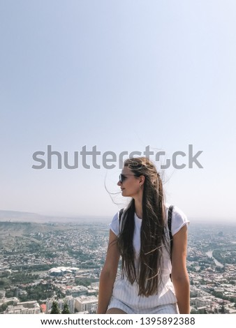Long hair woman turned head to city panoramic view. Girl in white clothes. Freelance lifestyle concept. Waving hair on the wind. Wind in the hair. Tbilisi panorama view.  #1395892388