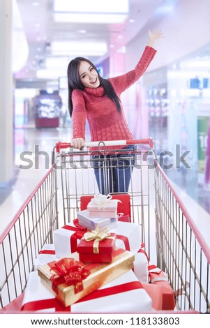 Long hair woman with christmas boxes in the trolley is shopping at the mall