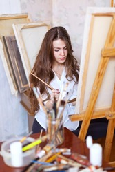 Long-haired  artist paints on canvas with oil colors