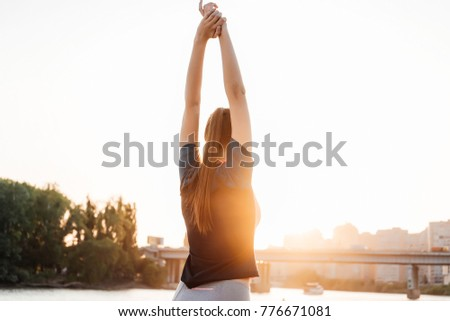 long-haired athletic girl kneading muscles before jogging against the backdrop of the sunset and the river #776671081