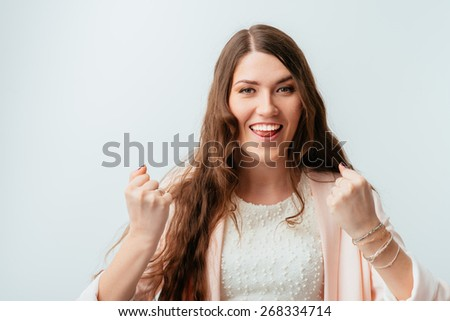 long-haired beautiful brunette girl happy with fists, isolated on a white background #268334714