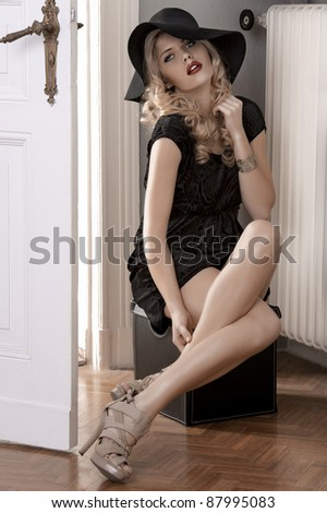 long haired blonde sitting in a doorway of an old fashioned house wearing a black dress and a huge hat