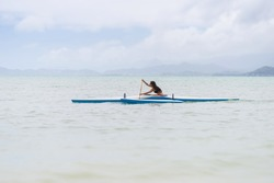 Long haired brunette female paddling a sport outrigger canoe at Kualoa Beach on the Oahu east shore