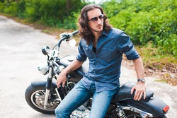 Long-haired brunette guy in sunglasses jeans and a denim shirt posing on a black custom motorcycle