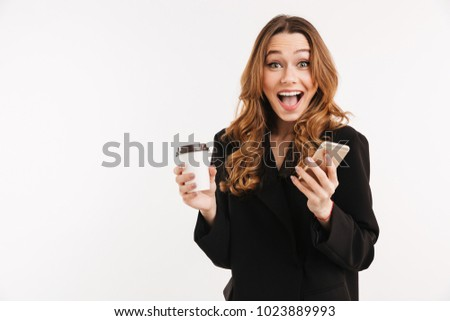 Long-haired brunette woman in black outfit smiling on camera while holding smartphone and takeaway coffee in hands isolated over white background