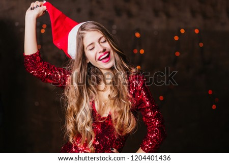 Long-haired brunette woman taking off santa claus hat after photoshoot. Indoor portrait of graceful curly female model in party attire fooling around on brown background.