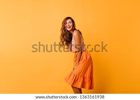 Long-haired curly woman in bright outfit expressing positive emotions. Romantic female model in orange skirt dancing on yellow background.