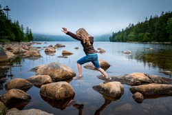 Long haired female child playfully hopping between a series of orange rocks on a serene lake against an overcast gray blue sky and framed by a tree lined coast.