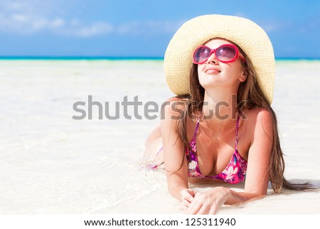long haired girl in bikini and straw hat and sunglasses on tropical philippines beach