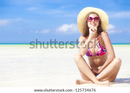 long haired girl in bikini and straw hat enjoying sun on tropical boracay beach